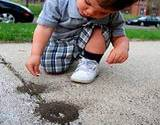 photo of little boy playing outside with ant hills
