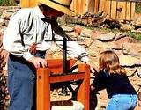 a man in a straw hat with little girl operating an apple press for vinegar making