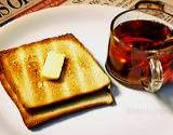photo of a cup of black tea with buttered toast