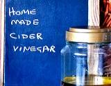 a homemade jar of apple cider vinegar with chalkboard behind it with words home, made, cider, vinegar