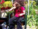 photo of a girl sitting in a greenhouse full of plants and suffering from hay fever