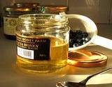 a beautiful photo of an opened jar of honey, a teaspoons with honey and a golden lid laying beside the jar