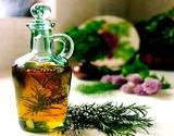 a sprig of rosemary laying next to a glass bottle of olive oil
