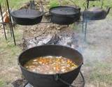 homemade soup cooking outdoors in cast iron pot
