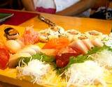 photo of a cutting board with variety of sushi being prepared with rice vinegar