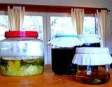a photo of home canned jars with vinegar and pickles vegetables