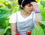 photo of a young lady working in her garden and showing signs of allergy headache