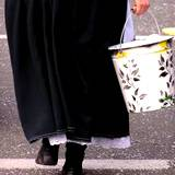 Amish women carrying bucket