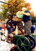 A photo of a man pour apples into an apple cider press