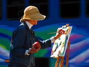 photo of a women painting on canvas outdoors to relieve headache symptoms stress