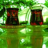 photo of two tall glasses of ice black tea sitting outdoors