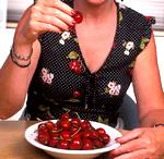 women eating a plate full of cherries