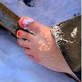photo of a woman's bare foot in the snow a natural remedy for cold feet