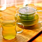 photo of a glass pot full of brewed green tea and a cup of green tea