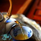 photo of herbal tea pot pouring a cup of herbal tea as an excellent source for natural hair loss