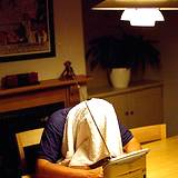photo of a man holding his head over a hot steam bowl of water with towel over his head