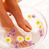photo of woman soak feet in medicinal chamomile tea
