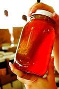 photo of a woman's hands holding a homemade jar of honey with the honeycomb inside