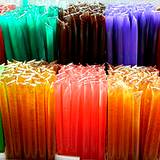 A photo of a display of honeysticks in various colors