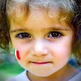 Little Italian girl with Italian flag painted on her cheek