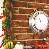 Italian kitchen red brick wall, clock and dried peppers hanging