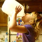 ;Little girl drinking milk from a gallon jug