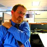 photo of man working in office rubbing shoulder for neck pain relief