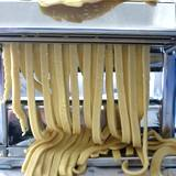 Pasta machine rolling out noodles for cooking pasta