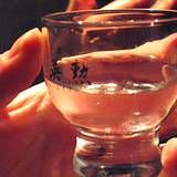 photo of a woman's hand holding a glass of sake