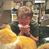photo of a man sneezing and a cat sitting nearby typical pet allergy