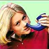 photo of a young woman using a neti-pot for hay fever relief