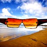 photo of a pair of sunglasses with beach view a natural way to prevent sun damage