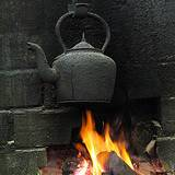 photo of a black cast iron tea pot over a fire in a fireplace brewing a pot of black tea