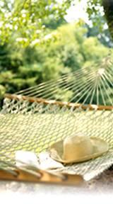 photo of a back yard hammock with straw hat sitting on it
