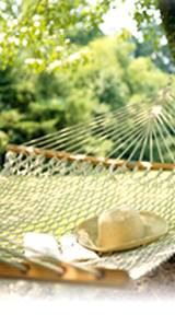 photo of a back yard hammock with straw hat sitting on it