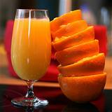 photo of stack of squeezed half oranges with glass of orange juice good source to avoid vitamin deficiency